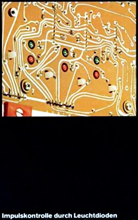 Ausschnitt aus einer Werbung der Siebziger Jahre. Im oberen Bereich des Bildes eine Platine mit sechs sichtbaren LEDs. Darunter der Text: Impulskontrolle durch Leuchtdioden -- Der Text ist einfach abgeschnitten, der Kontext zerstört -- Die Werbung ist übrigens für die neue Geldspielgeräte-Serie von Wulff, die im Jahr 1976 mit dem Lord begann. Ein Kennzeichnen waren völlig neue, sehr viel leichter wartbare mechanische Zählwerke, und die abgeschnittene Reklame pries in vollständiger Form diese Zählwerke an. Die oben abgebildete Platine ist die Rückseite der Zählwerksplatine. Man beachte übrigens den Verlauf der Leiterbahnen. So etwas haben die Ingenieure damals noch nicht am Computer gemacht, und man sieht teilweise, wie das Projekt gewachsen ist.