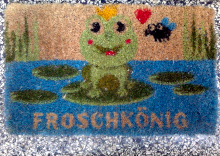 Fußabtreter vor einer Haustür, mit Froschkönig-Motiv