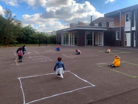 Pause an einer Grundschule. Auf dem Schulhof sind Quadrate markiert, und jedes Kind hält sich in seinem Quadrat auf, mit großem Abstand von den anderen Kindern.
