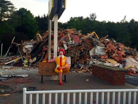 Schwierig zu beschreibendes Foto. Ronald McDonald sitzt auf einer Bank vor einem riesigen Müllberg