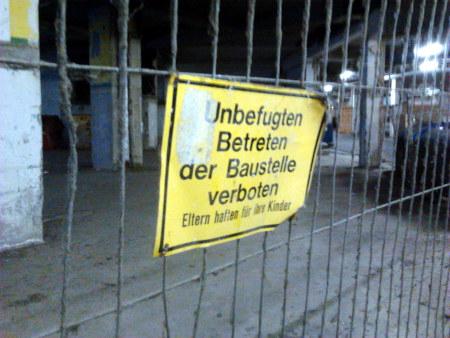 Ein von der Zeit mitgenommener, angerosteter und sehr verdreckter Bauzaun mit einem Schild: Unbefugten Betreten der Baustelle verboten! Eltern haften für ihre Kinder