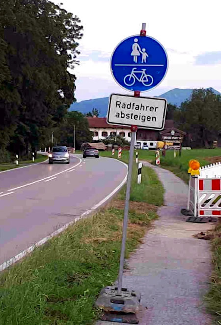 Verkehrtzeichen Geh- und Radweg (VZ 240) an einem engen Radweg, also ausgeschilderte und mit Bußgeldern durchgesetzte Benutzungspflicht für Radfahrer, mit Zusatzschild darunter: 'Radfahrer absteigen'.