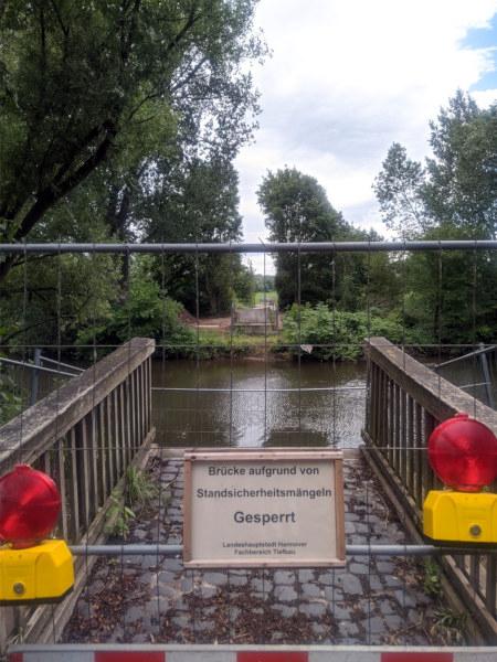 Vor einer nicht mehr vorhandenen Brücke eine Absperrung, und an der Absperrung ein Schild: Brücke aufgrund von Sicherheitsmängeln gesperrt