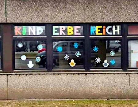 Fenster, die von innen mit bunten Buchstaben beklebt sind: KIND - ERBE - REICH