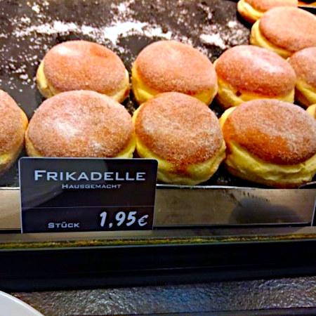 Krapfen in einem Regal, davor ein Schild 'Frikadellen, hausgemacht, Stück 1,95 €