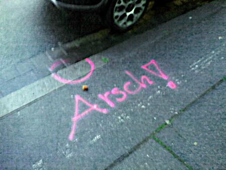 Graffito: Am Rand einer Straße ist eine Stelle markiert und daneben das Wort 'Arsch!' gesprüht worden. Offenbar wird die Stelle jetzt freigehalten