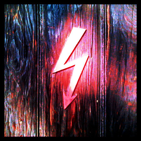 Stark mit Gimp bearbeitetes Foto eines alten Warnzeichens vor Hochspannung (ein roter Blitz) auf einer Holztür.