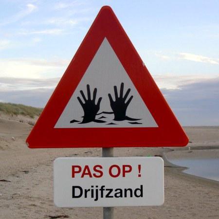 Warnschild an einem niederländischen Strand. Das Schild ist im Stile eines Verkehrszeichens. Es ragen nur noch die Hände aus dem Boden. Darunter steht: Pas op! Drijfzand