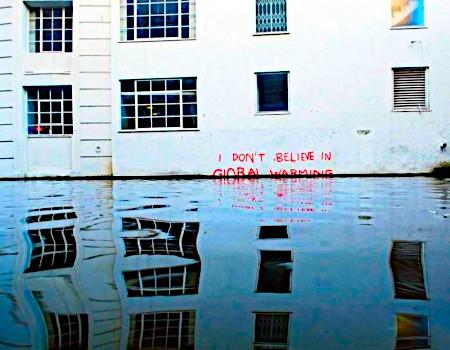 Hauswand mit einem Graffito 'I do not believe in global warming', das in seiner unteren Hälfte bereits vom Hochwasser erreicht wurde
