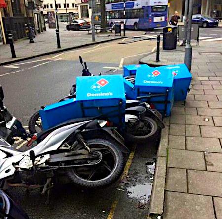 Mehrere nebeneinaderliegende, umgekippte Domino-Mofas mit den typischen Domino's-Kästen auf dem Gepäckträger