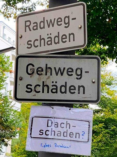 Zwei Schilder übereinander: 'Radwegschäden' und 'Gehwegschäden'. Dazu ein ausgedrucktes Schild in Klarsichtfolie: 'Dachschaden' liebes Bezirksamt?