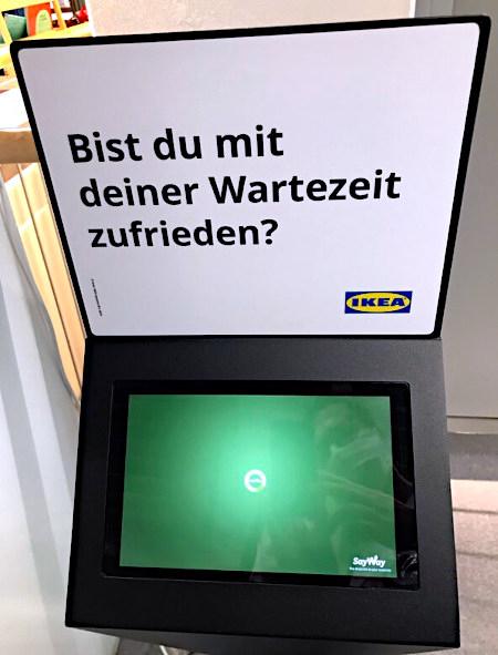 Ein Touchscreen-Terminal für Kundenfeedback, das einen leeren Bildschirm mit einer Warteanimation zeigt und nicht mehr bedienbar ist. Darüber der große Text: Bist du mit deiner Wartezeit zufrieden? Ikea
