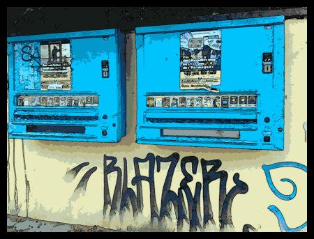 Zwei Kondomautomaten an einer schmucklosen Wand. Darunter ein Graffito: Blazer