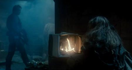 Szene aus 'Terminator'. Eine Frau sitzt vor einem kaputten Fernseher, in dessen Inneren ein Lagerfeuer brennt, während im Hintergrund ein Bewaffneter vorbeigeht, weil der Krieg gegen die Maschinen läuft.