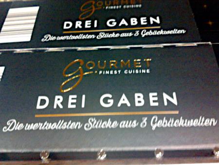 Verpackung im Regal eines Supermarktes: Gourmet -- Finest Cuisine -- Drei Gaben -- Die wertvollsten Stücke aus 3 Gebäckwelten