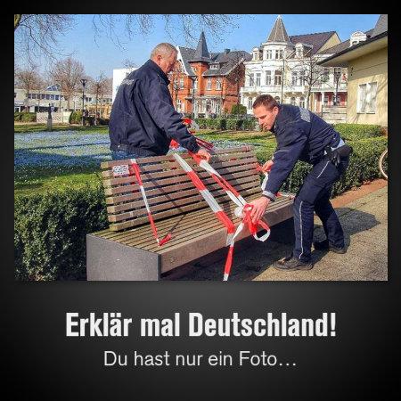 Angestellte des Ordnungsamtes sperren eine Sitzbank in einem Park mit Flatterband ab. Dazu der Text: Erklär mal Deutschland! Du hast nur ein Foto…