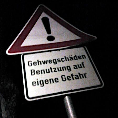 Verkehrszeichen Allgemeine Gefahrstelle, mit Zusatzschild: Gehwegschäden -- Benutzung auf eigene Gefahr