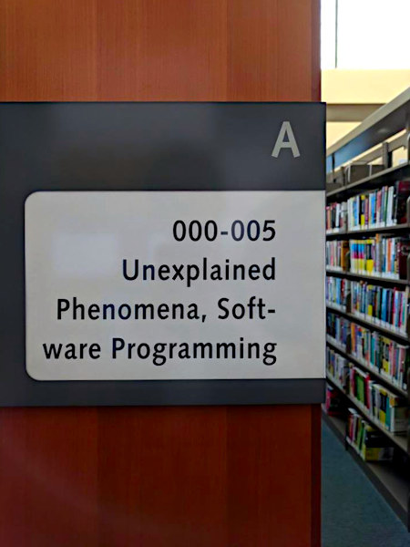Wegweiserschild am Regal einer Bücherei: A 000-005 -- Unexplained Phenomena, Software Programming
