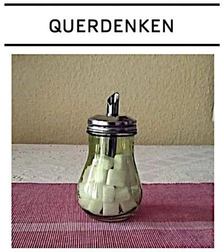 Foto eines Zuckerstreuers, der mit Zuckerwürfeln gefüllt ist. Darüber das Wort 'Querdenken'.