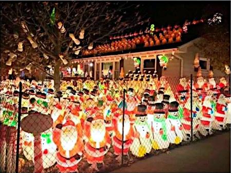 Absurdes Foto eines umzäunten Grundstückes, das mit leuchtenden Weihnachtsmännern und Schneemännern vollgestellt ist