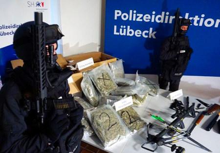 Zwei Polizeibeamte stehen mit präsentiertem Maschinengewehr neben einem beschlagnahmten Cannabis-Fund