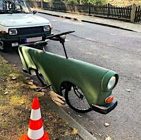 Fahrrad, dass mit einer lackierten Blechverkleidung wie ein Auto versehen ist, einschließlich Scheinwerfer und Stoßstange. Dazu ein Auto-Lenkrad statt eines Fahrradlenkers.