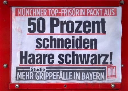 Werbung an einem Bildzeitungs-Verkaufsautomaten in München -- Münchner Top-Frisörin packt aus: 50 Prozent schneiden Haare schwarz!