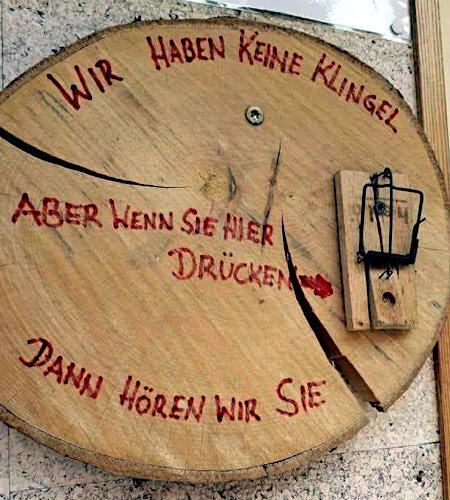 Unbeschreibliches Foto einer Holzplatte, auf die eine Mausefalle geklebt und aufgespannt wurde, umgeben vom Text: Wir haben keine Klingel. Aber wenn sie hier drücken, dann hören wir sie auch