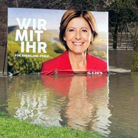 Unbeschreibliches Foto eines SPD-Wahlplakates für den Landtagswahlkampf in Rheinland-Pfalz mit der Spitzenkandidatin und dem Werbespruch 'Wir mit ihr', dass im Hochwasser steht und sich von der Plakatfläche löst