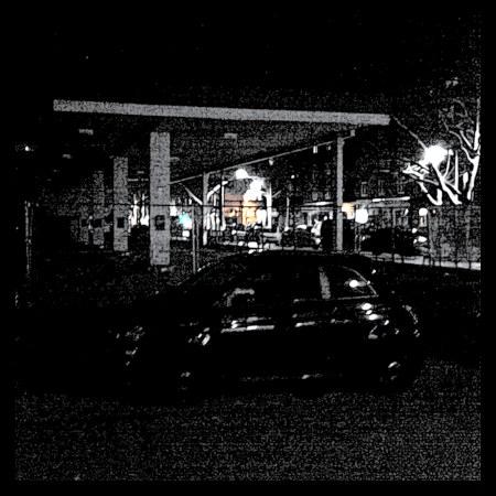 Stark mit Gimp bearbeitetes Bild eines Autos, das vor einem Absperrzaun parkt, der eine geschlossene Tankstelle sichern soll.