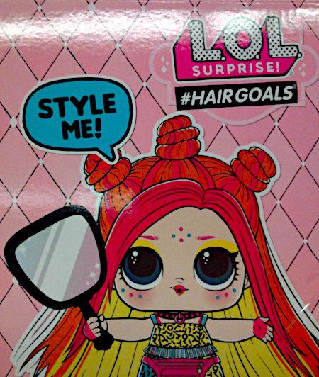 Unbeschreibliche Spielzeugverpackung. LOL-Surprise #Hairgoals mit dem Motiv eines beinahe nur aus Haaren bestehenden Mädchens, das einen Spiegel in der Hand hält und 'Style me' einfordert