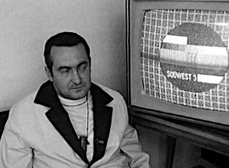 Jemand sitzt vor einem Fernseher, der ein Testbild (stark modifiziertes Philips-Testbild PM5540, sehr ähnlich zum damaligen Testbild des isländischen Fernsehens Sjónvarpið) des dritten Programmes des Südwestfunks zeigt