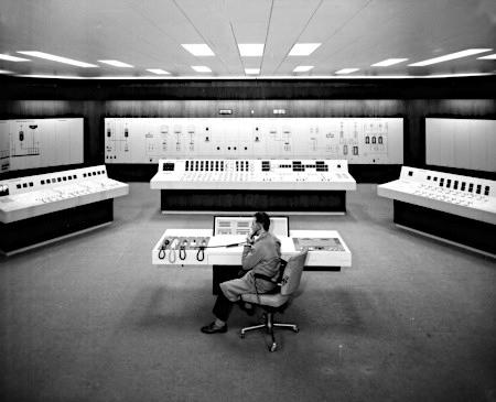 Foto aus dem CERN im Jahr 1970. Ein Mann sitzt in einem klinisch rein aussehenden Kontrollraum umgeben von großen Datenverarbeitungsanlagen