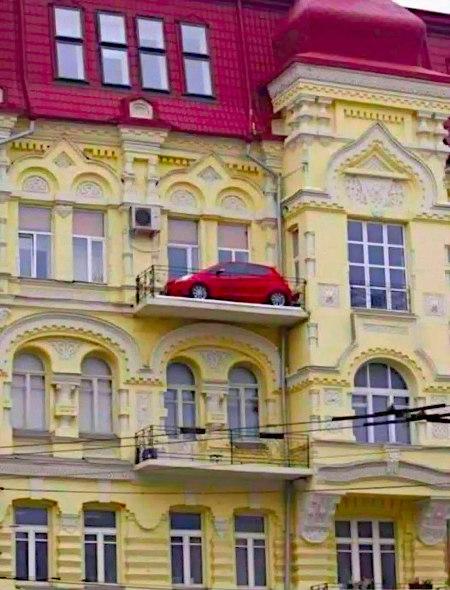 Ein Auto, das auf einem Balkon abgestellt ist.
