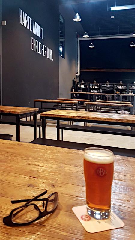 An der Wand steht groß 'Harte Arbeit, Ehrlicher Lohn', auf einem Tisch steht ein Glas Bier.
