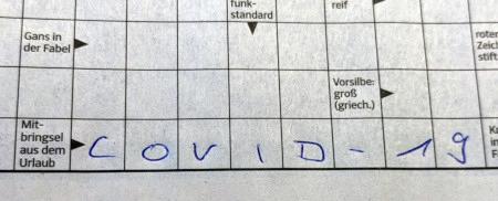Foto eines Kreuzworträtsels aus einer Zeitung. Als Antwort für 'Mitbringsel aus dem Urlaub' wurde C O V I D - 1 9 eingetragen.