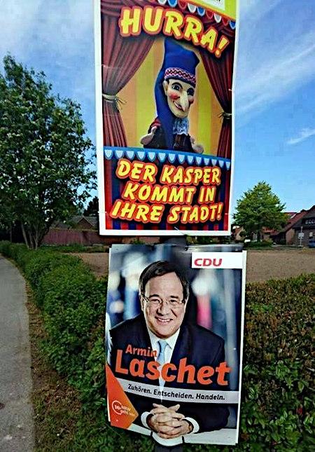 Zwei Plakate übereinander an einem Laternenmast. Oben: Hurra! Der Kasper kommt in ihre Stadt! Unten: CDU. Armin Laschet. Zuhören. Entscheiden. Handeln.
