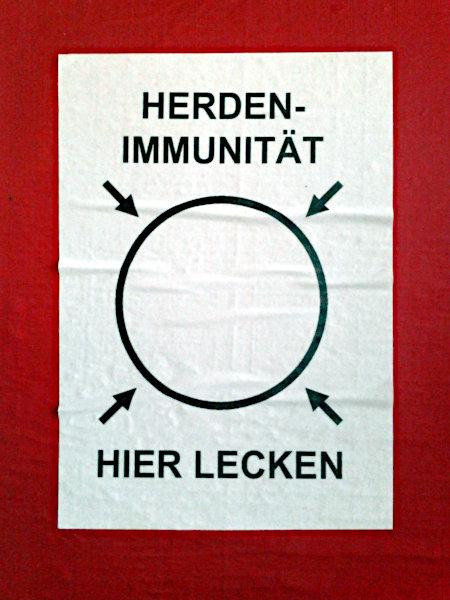 Aufkleber. In der Mitte ein Kreis, auf den vier Pfeile zeigen. Über dem Kreis das Wort: Herdenimmunität, unter dem Kreis: Hier lecken
