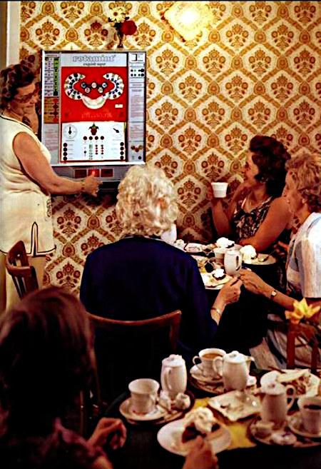 Foto aus der Reklame für das NSM-Geldspielgerät Rotamint Exquisit Super. Eine Szene im Café, und das ausschließlich weibliche Publikum schaut bei Kaffee und Torte einer Spielerin zu, die sich bei so viel Ruhm gar nicht mehr für das Spiel zu interessieren scheint. Das alles in Stil und Farben der Siebziger Jahre, einem Jahrzehnt, in dem die Augen kotzen wollten. Stilecht und überzeugend mit Plastikblumen auf dem Geldspielgerät.