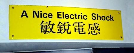 Chinesisches Schild über einem Eingang, mit englischer Übersetzung des Textes: A nice electric shock