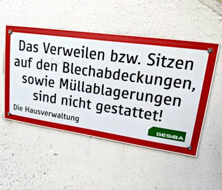 Schild: Das Verweilen bzw. Sitzen auf den Blechabdeckungen, sowie Müllablagerungen sind nicht gestattet! Die Hausverwaltung