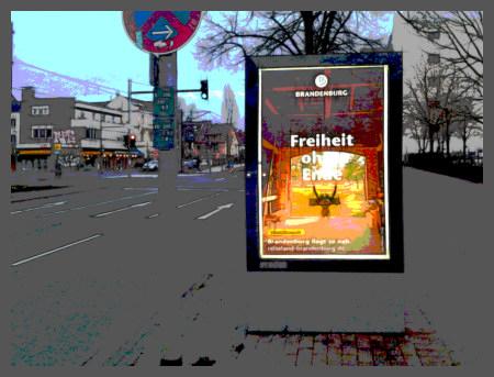 Stark mit Gimp bearbeitetes Foto einer leuchtenden Werbewand in einer grauen Stadtlandschaft. Der Claim in der Werbung für Urlaub in Brandenburg lautet 'Freiheit ohne Ende'.