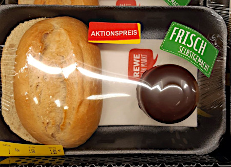 Ein aufgeschnittenes Brötchen und ein Schaumkuss in einer Klarsichtverpackung aus Plastik (bei Rewe) mit Aufkleber: Frisch selbstgemacht