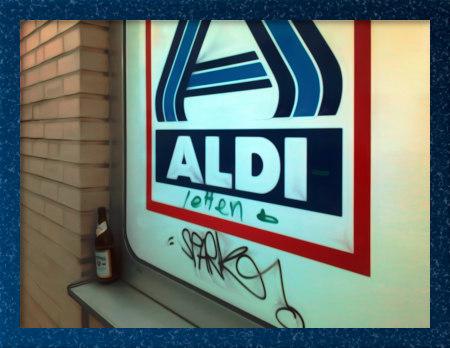 Mit Gimp bearbeitetes Foto einer Flasche Bier, die vor einem Fenster steht, das von innen mit einer Reklamefolie von Aldi Nord beklebt wurde