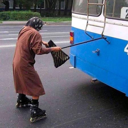 Unbeschreibliches Foto einer alten Frau auf Inline-Skates, die sich mit ihrem Spazierstock hinten an einem Omnibus eingehakt hat