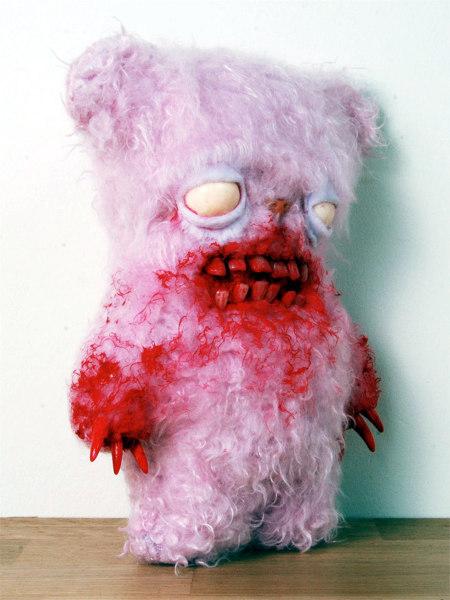 Unbeschreibliches Foto eines hellrosafarbenen Teddybären mit leeren Augen, Zähnen im Mund, Krallen und blutverschmiertem Fell