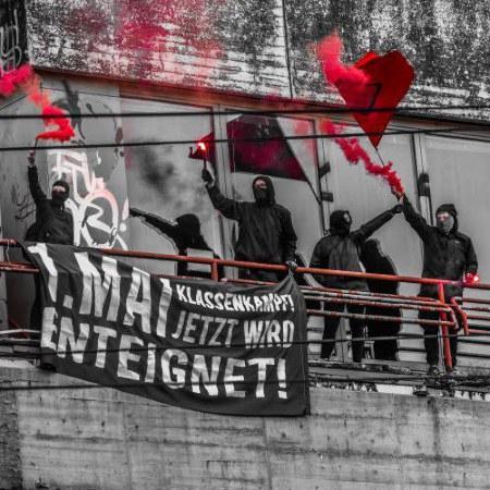 Demonstranten stehen am 1. Mai in der Ruine des Ihmezentrums in Hannover-Linden, mit Transparent: 1. Mai -- Klassenkampf -- Jetzt wird enteignet