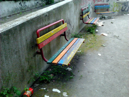 Foto vom Spielplatz an der Ihmezentrum-Ruine in Hannover-Linden. Die bunt bamalten Bänke, schon wieder im Zerfall begriffen und teilweise kaputt, von Müll umgeben, machen die Tristesse nur um so schlimmer fühlbar