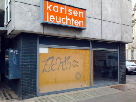 Leerstehendes Ladengeschäft »Karlsen Leuchten« auf der Hildesheimer Straße, Hannover. Ein Schaufenster ist eingeworfen und provisorisch mit Sperrholz geflickt, auf dem Holz ein ungelenkiges Graffito, das keinen Sinn ergibt.