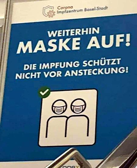 Ausgehängtes Plakat in Basel -- Corona-Impfzentrum Basel Stadt -- Weiterhin Maske auf! -- Die Impfung schützt nicht vor Ansteckung!